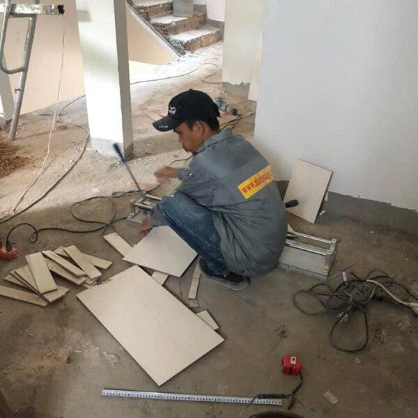 Nhân công đang tiến hành ốp gạch vào tường