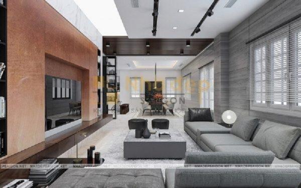 Phòng khách trông thông thoáng và tiện nghi hơn rất nhiều khi thiết kế bộ sofa hình chữ L, chiếc bàn trà hình vuông cùng tông màu với thảm trải nhà và sofa, kệ tivi được áp sát tường đã tạo nên một bố cục phòng khách khoa học.